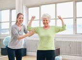 stock photo of arm muscle  - Portrait of a fit old woman flexing her arms and showing her muscles with personal trainer at gym - JPG