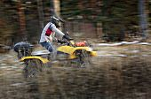 image of four-wheel drive  - Horizontal motion blurred action shot of a man in helmet and safety goggles riding four - JPG