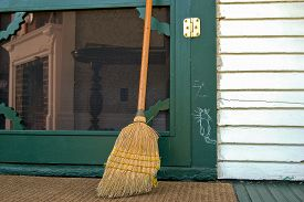 foto of hobo  - Old worn out broom leaning on a green door with hobo sign - JPG
