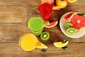 image of fruit-juice  - Fresh juices with fruits on wooden table - JPG
