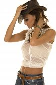 stock photo of cowgirl  - A cowgirl looking down holding on to the top of her hat - JPG
