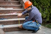 foto of measuring height  - Young builder checking stairs height by measuring tape - JPG