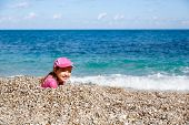 pic of children beach  - Girl buried in beach pebbles smiling and enjoying free time on the beach dressed in wetsuit and a hat for sun protection - JPG