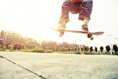 picture of skateboard  - young skateboarder doing skateboarding trick ollie outdoor - JPG