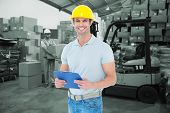 stock photo of pallet  - Happy architect holding clip board against warehouse worker loading up pallet - JPG