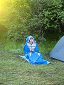 picture of sleeping bag  - The man is resting in a sleeping bag on the background of tents and green forests - JPG