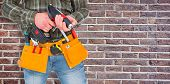 picture of hammer drill  - Manual worker holding gloves and hammer power drill against red brick wall - JPG