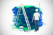 image of paint pot  - Man with paint roller standing by ladder against blue and green paint - JPG