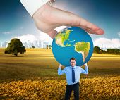 foto of presenting  - Hand presenting against field with tree and city on the horizon - JPG