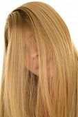 stock photo of peek  - a woman with her blond hair over her face peeking through - JPG