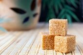 picture of sugar cube  - Three cubes of cane sugar on the mat - JPG