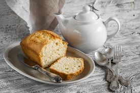 pic of milkman  - simple cake on an oval platter a teapot and silver cutlery on a light wooden background - JPG