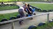 Teenager/Girl Playing/Pushing Boy On A Toy Tractor.Leisure.Children Playing poster