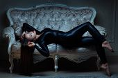 Girl In Latex Suit Is Lying On The Sofa. poster