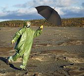 image of scoria  - The comical person in protective scientific overalls with an umbrella in a hand - JPG