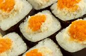stock photo of masago  - Masago eggs seen close up on a rice roll with the nori sea weed on the outside - JPG