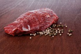 stock photo of peppercorns  - fresh raw beef meat steak with white and green peppercorn spice on walnut table - JPG