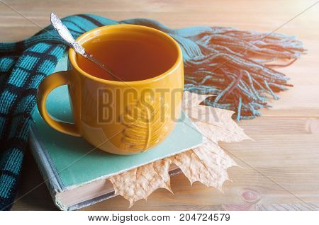 poster of Autumn still life. Cup of tea, worn book with dry maple autumn leaf, green scarf on the wooden background - autumn still life. Autumn background. Autumn concept. Vintage autumn still life. Autumn composition.