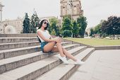 Attractive Carefree Gorgeous Lady With Bronze Skin Is Posing In Town, On Stroll, Sitting On Concrete poster