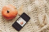 Phone With Photo Of Pumpkin And Leaf With Cute Pumpkin On Warm Sweater, Top View. Instagram Blogging poster