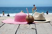 Beach Vacation. Sun Hat. Beach scene. Summer accessories. Summer concept. Coconut with a straw to dr poster