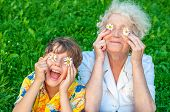 Happy Grandmother And Grandchild Fooling Around The Lawn Of Putting Chamomiles Instead Of Eyes. Fami poster