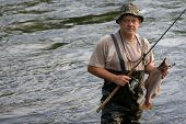 stock photo of early 50s  - Fisherman caught a salmon  - JPG