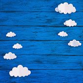 Paper Handmade Crafts Clouds On The Blue Wood Background. Top View, Copy Space. poster