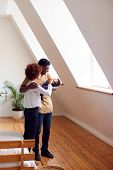 Loving Parents Holding Newborn Baby At Home In Loft Apartment poster