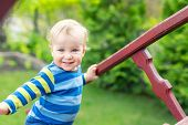 Portrait Of Cute Mischievous Caucasian Blond Baby Boy Holding Wooden Banister Climbing Staircase At  poster