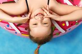 Closeup Cute Little Girl In A Bathing Suit Lying On A Donut Inflatable Circle. Baby Upside Down. Sum poster