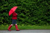 Photo of a woman in red walking along a road with her umbrella up as it starts to rain on an overcas