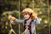 Cute Child In Climbing Safety Equipment In A Tree House Or In A Rope Park Climbs The Rope. Cargo Net poster
