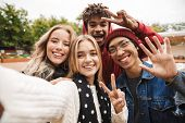Group if cheerful multiethnic friends teenagers spending fun time together outdoors, taking a selfie poster