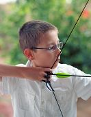 image of fletching  - Close up of a young boy drawing back a bow and arrow - JPG