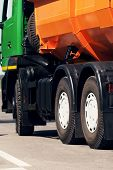 stock photo of chassis  - Orange dump truck chassis close to the road - JPG