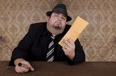 stock photo of mafia  - Smoking gangster holding brown envelope - JPG
