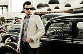 Young Handsome Man, Model Of Fashion, Wearing Jacket And Shirt With Old Cars
