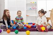 stock photo of preschool  - Cute kids playing in the room with toys - JPG