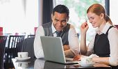 stock photo of cafe  - Happy business team working together in a cafe with laptop - JPG