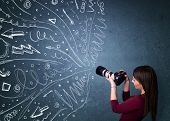 Photographer girl shooting images while energetic hand drawn lines and doodles come out of the camer