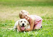foto of caress  - A little blond girl with her pet dog outdooors in park - JPG