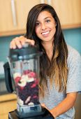 Beautiful Young Woman Making Fruit Smoothie in Blender