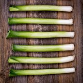 Baby leeks on old wood background, vintage style with intentional vignette