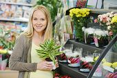Young smiling woman buyer choosing flower in superstore shop