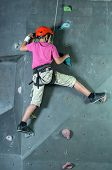 stock photo of climbing wall  - Child climbing on a wall in a climbing center - JPG