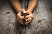 stock photo of mary  - A person praying holding a rosary in the hands on wood background - JPG