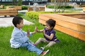 stock photo of fountain grass  - Brother and sister sitting on the grass and clap each other hands - JPG