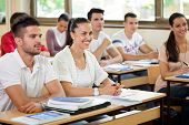 stock photo of classmates  - young students in classroom listening a lecturer - JPG