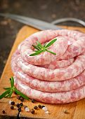 stock photo of charcuterie  - Fresh raw sausage on the old wooden background - JPG
